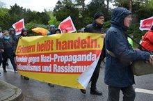 """Demo-Teilnehmer*innen tragen ein Transparent mit der Aufschrift """"Erinnern heißt handeln, handeln gegen Nazi-Propaganda, Antisemitismus und Rassismus"""""""